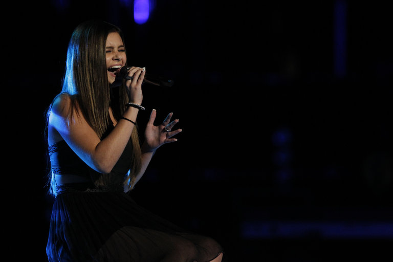 "Not content to play it safe, Jacquie next took on a stripped-down version of the dance music hit ""Clarity"" by Zedd. The tiny teen with the big voice blew America away by turning the song into a soulful piano ballad, and moved on to the next round."
