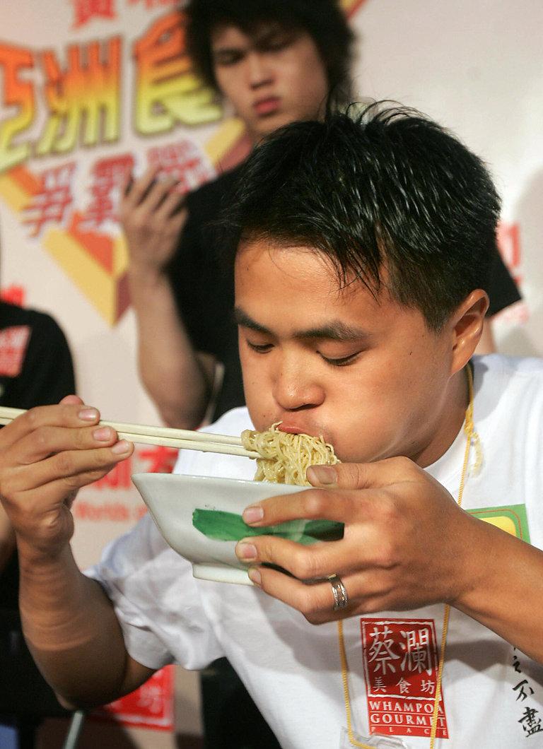 A local contestant wolfs down noodles du