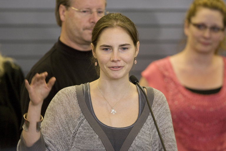 Amanda Knox waves to supporters as she m