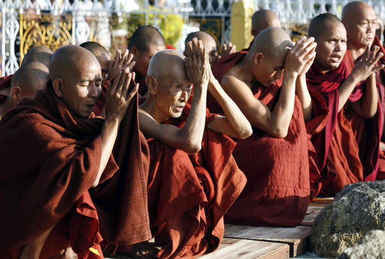 Buddhist monks chant in front of a golde