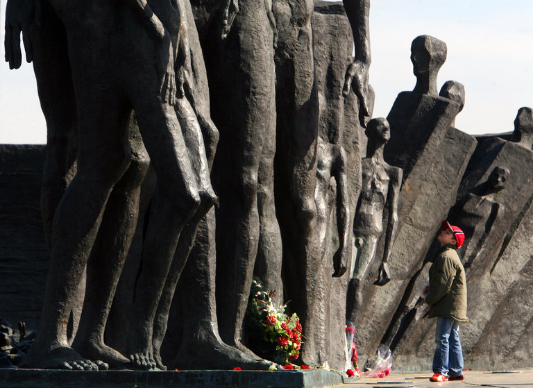 A boy looks at a monument to the victims