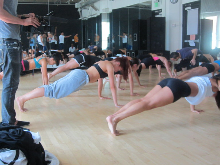 The girls challening the boys to who can do more push ups.