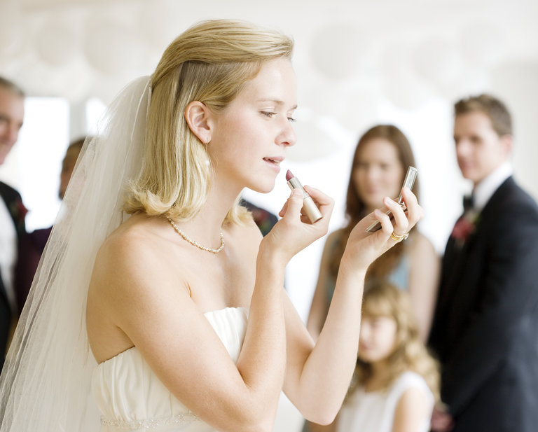 bride applying lip stick at her wedding