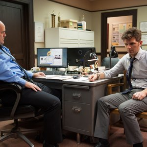 """Parks and Recreation - Ben Wyatt sits with Officer Killnose in a scene from episode 611, """"New Beginnings"""""""