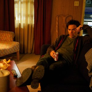 Revolution - Miles Matheson watches TV on a motel couch drinking a cold one
