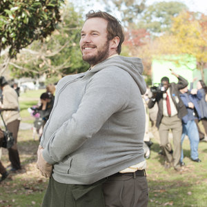 Parks and Recreation - Andy Dwyer smiles while hiding April in his hoodie from a swarm of bees