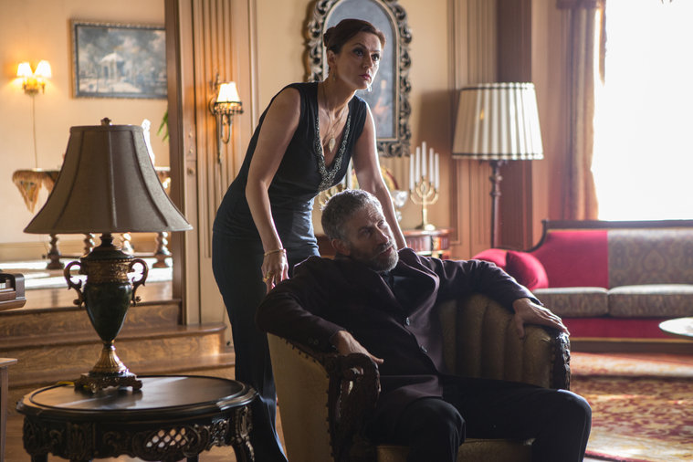 Grimm - Olga standing behind Myshkin sitting in chair from Red Menace