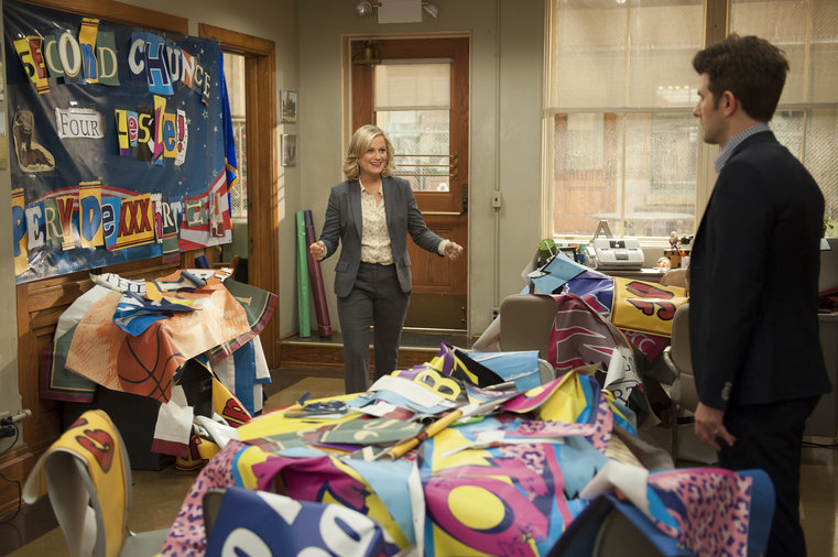 Parks and Recreation - Leslie in office showing Ben her comeback banner