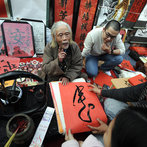 An elderly calligrapher (C) explains the