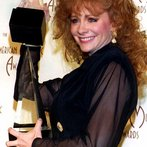 Country singer Reba McEntire holds two trophies sh