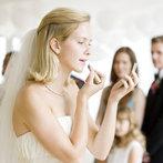 bride applying lip stick at her wedding
